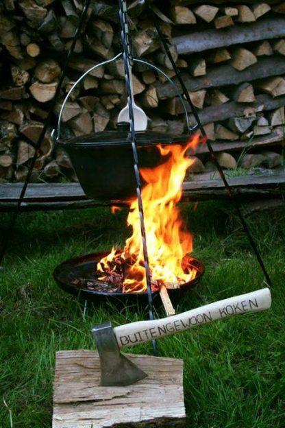 Emaille heksenketel aan driepoot boven een brandend houtvuur